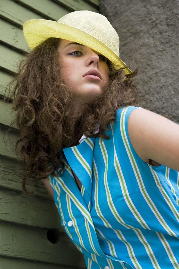 Dame med gul hatt og blåstripete kjole